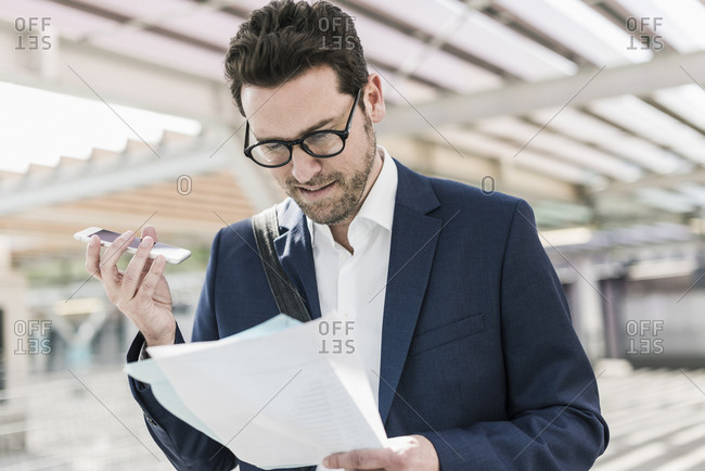 Businessman standing on parking level- reading documents- speaking notes on smartphone