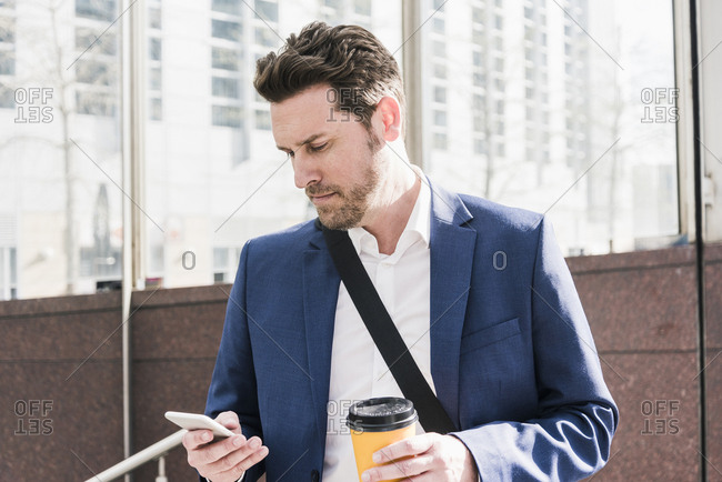 Businessman in the city- reading smart phone messages and holding cup of coffee