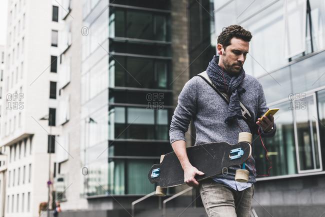 Businessman carrying skateboard- using smartphone and earphones