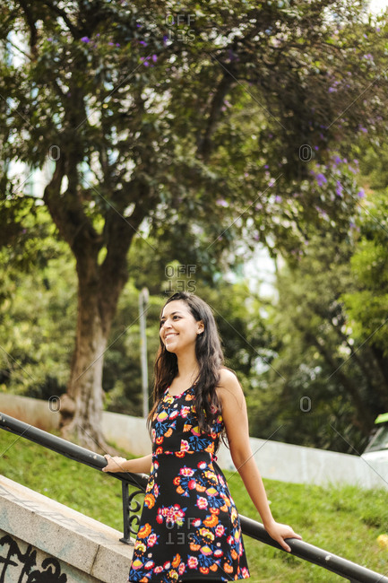 Smiling young woman wearing summer dress with floral design