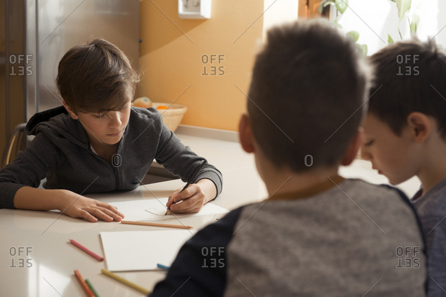 Three friends drawing with colored pencils in the kitchen