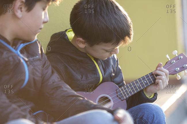 Boy playing ukulele while his friend watching him