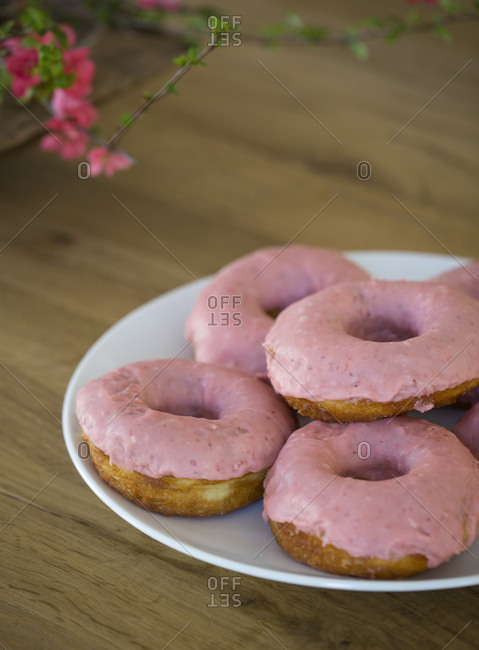 Plate of pink frosted doughnuts