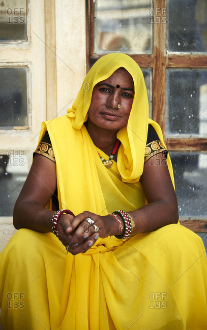 Jaipur, India - March 17, 2017: Indian woman sitting in yellow suri.
