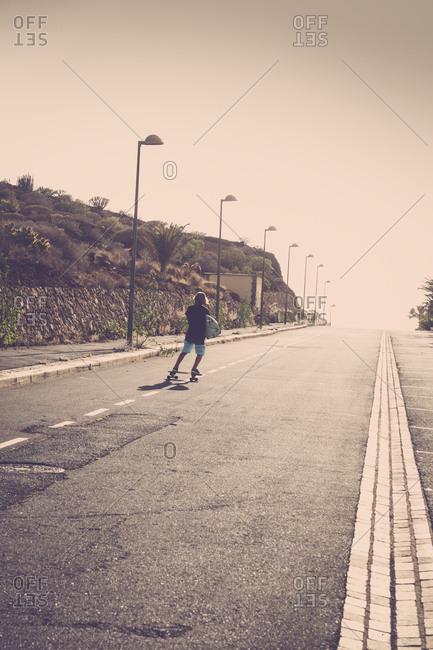 Boy riding a skateboard alone