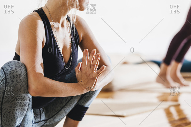 Woman with hands clasped crouching while performing yoga in studio