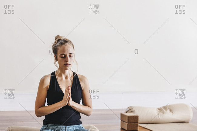 Relaxed young woman sitting in prayer position at yoga studio