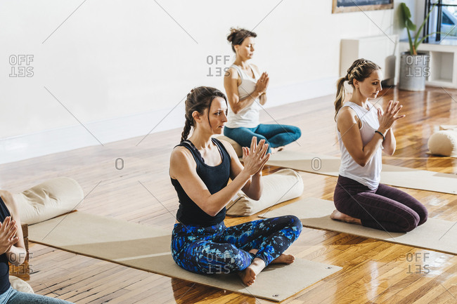 Women with hands clasped practicing yoga at studio