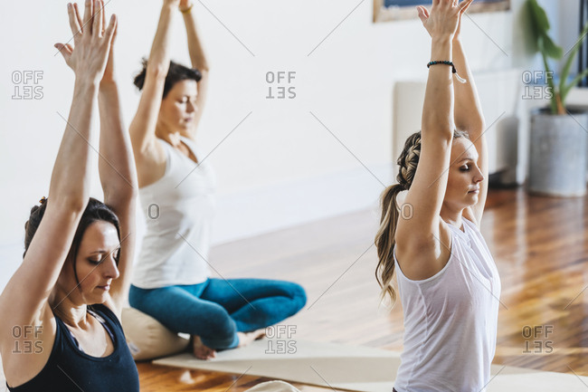 Women with hands clasped and eyes closed practicing yoga at studio