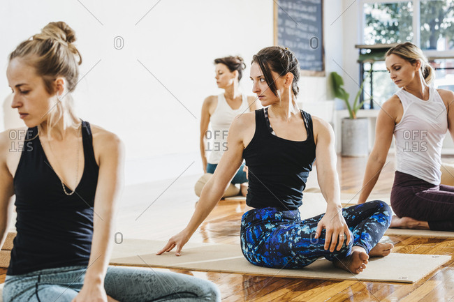Women practicing yoga while sitting on exercise mats in studio