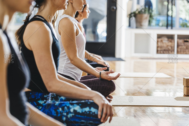 Midsection of women meditating in yoga studio