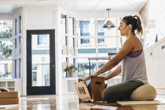 Female yoga instructor singing while playing harmonium in yoga studio