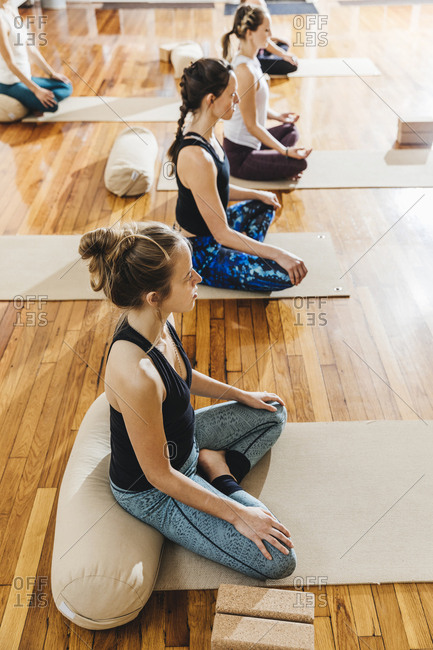 High angle view of women practicing yoga while sitting on exercise mats at studio