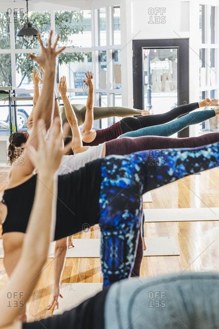 Women practicing yoga at brightly lit health club