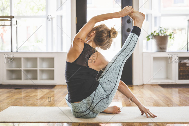 Rear view of flexible woman practicing yoga in studio
