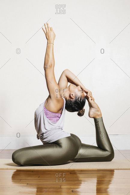 Flexible woman doing yoga in one-legged king pigeon pose