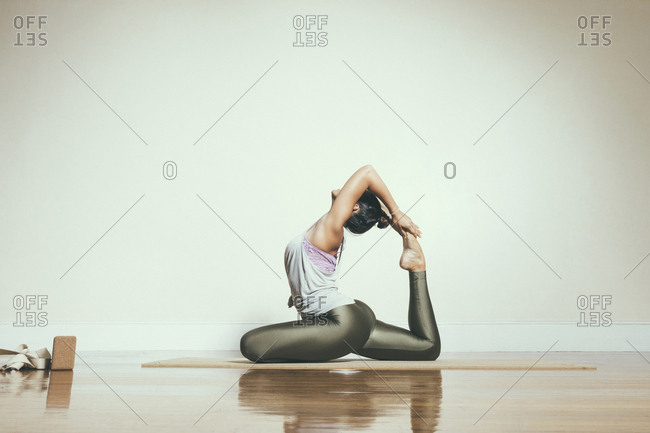 Side view of flexible woman doing yoga in one-legged king pigeon pose against white wall