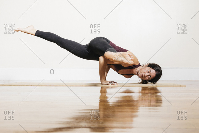 Woman practicing yoga in one legged arm balance with straight legs pose at studio