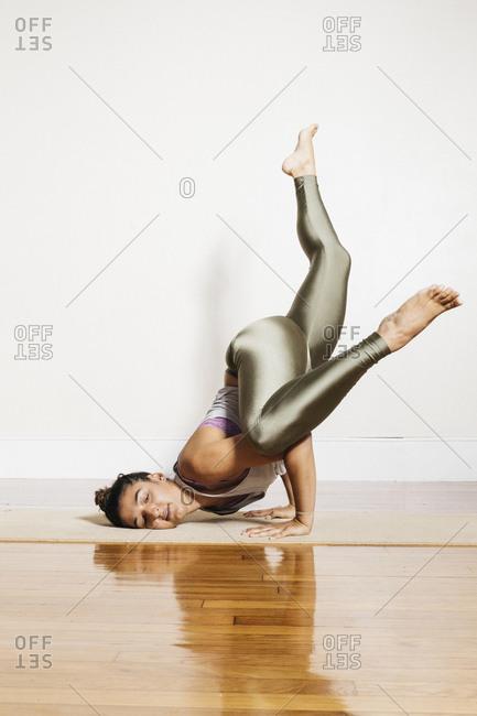 Flexible woman doing yoga against white wall at health club