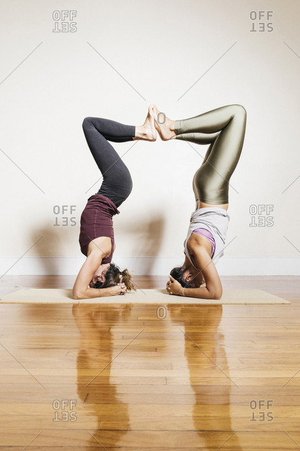 Side view of women joining each other's feet while doing headstands in gym