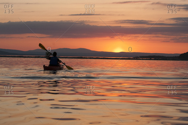 Woman kayaking on Lake Champlain at sunset in Burlington, Vermont