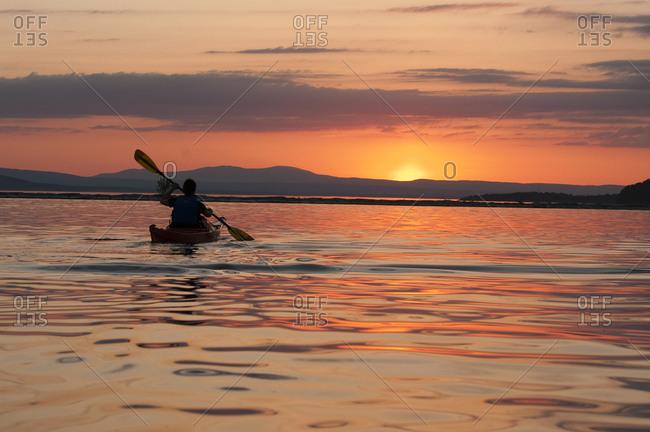 Woman kayaking on Lake Champlain at sunset in Burlington, Vermont