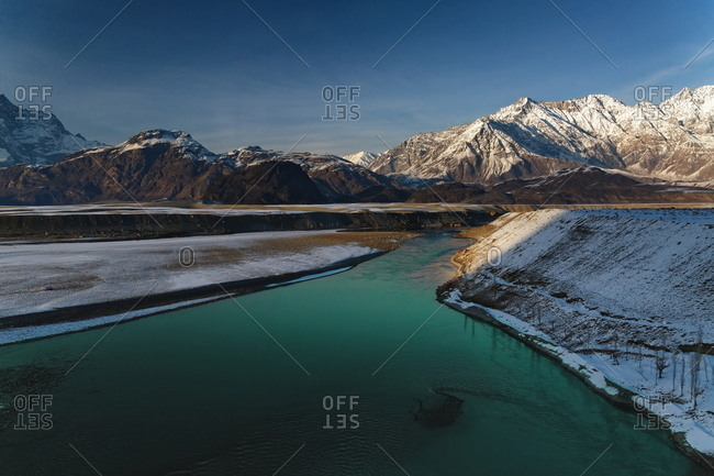 Green water of river with snowy mountains in background