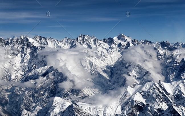 Clouds drifting over snowy mountain peaks