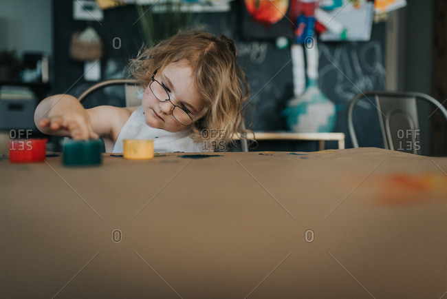 Little girl with glasses playing with finger paints at table