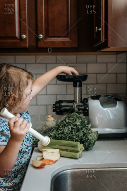 Young girl using juicer in kitchen