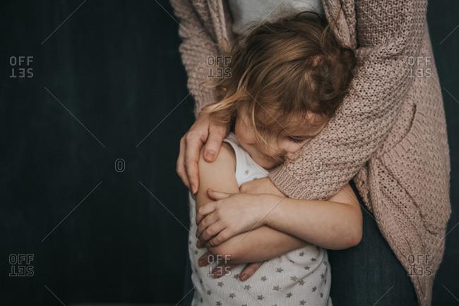 Mother hugging her toddler daughter