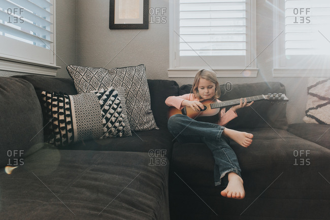 Young girl practicing guitar on couch