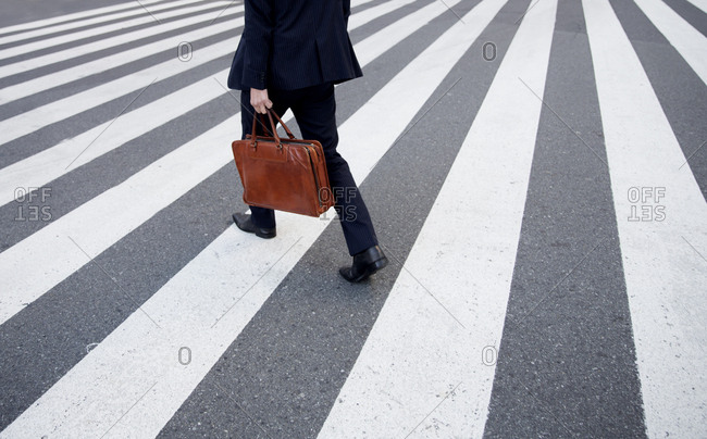 Businessman crossing the street in the Shinjuku area of Tokyo, Japan