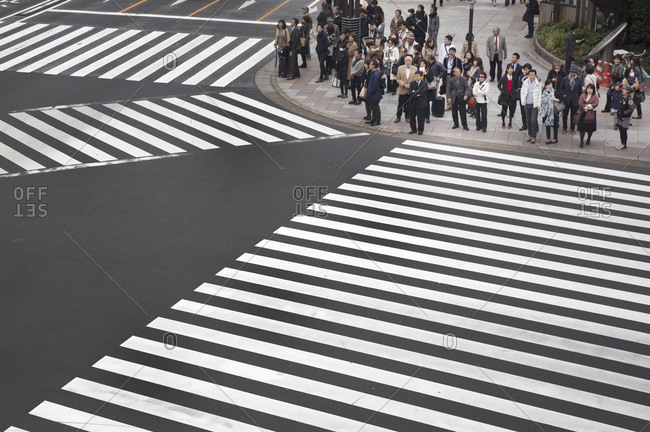 Tokyo, Japan - November 22, 2015: Many people waiting to cross the street at an intersection in the Ginza district