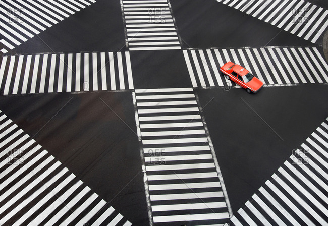 Car driving through an intersection with crosswalks in the Ginza district of Tokyo, Japan