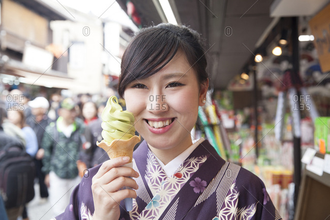 Kyoto, Japan - November 28, 2015: Portrait of a smiling Japanese young woman holding a green tea ice cream cone
