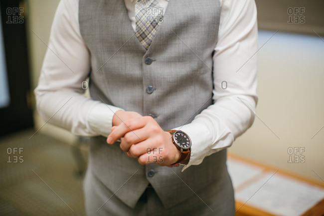 Man in a gray tuxedo putting on a watch