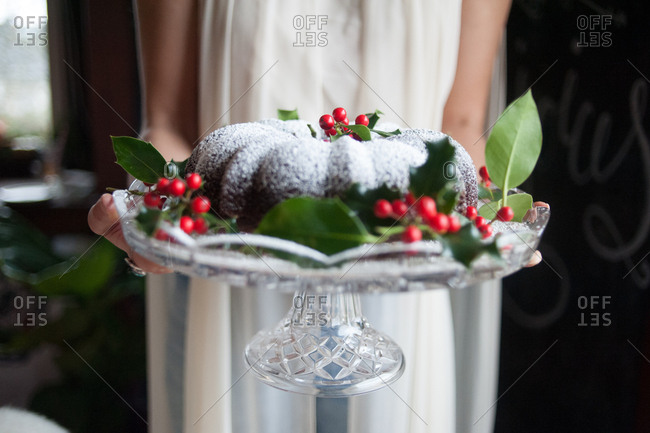 Woman holding a cake decorated with holly leaves and berries