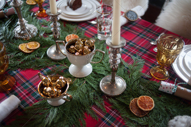 Candlesticks and glasses on a plaid table decorated for Christmas