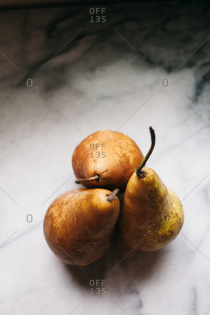 Three pears on a marble surface