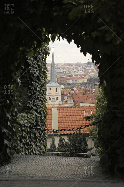 View of church and city seen through ivy covered archway, Prague, Czech Republic