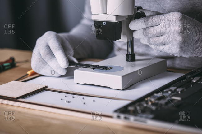 Detail image of technician examining random access memory with microscope at electronics store
