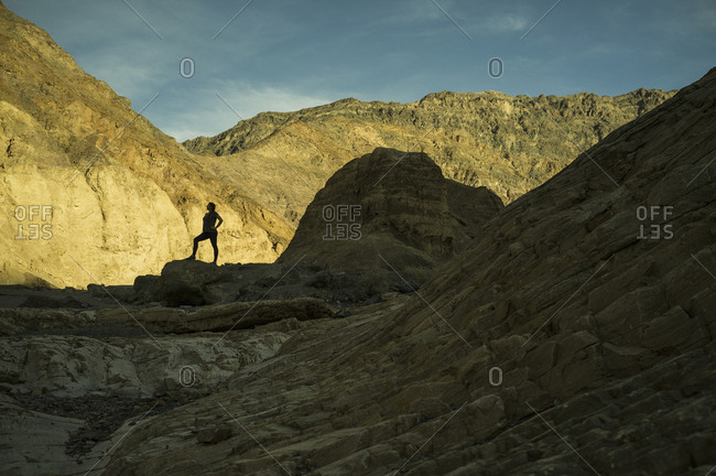 Silhouette of woman standing in rocky landscape, Death Valley, Nevada, USA