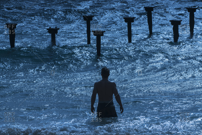 Rear view of man in sea at dusk