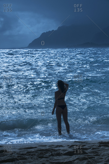 Rear view of woman standing on shore at beach