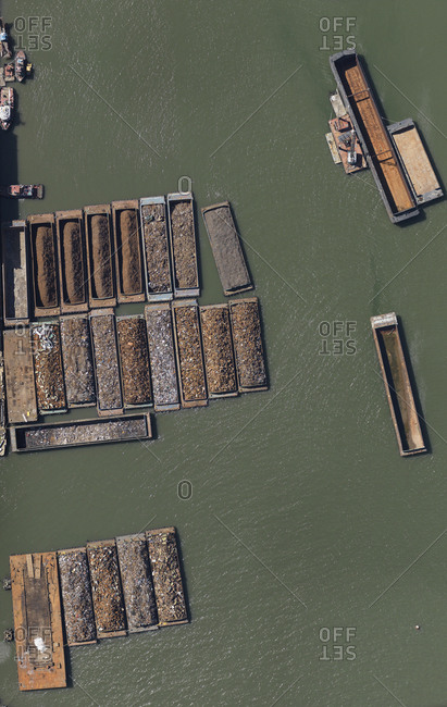 Aerial view of rocks and ores on barges in sea