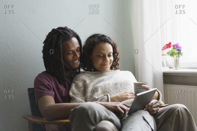 Young multi-ethnic couple using digital tablet while sitting on armchair at home