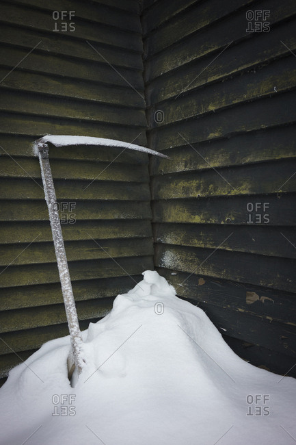Ice axe in snow against wall