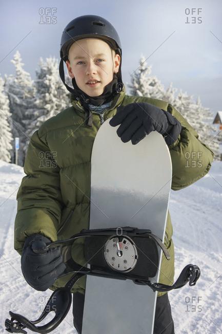 Portrait of boy in ski gear holding snowboard