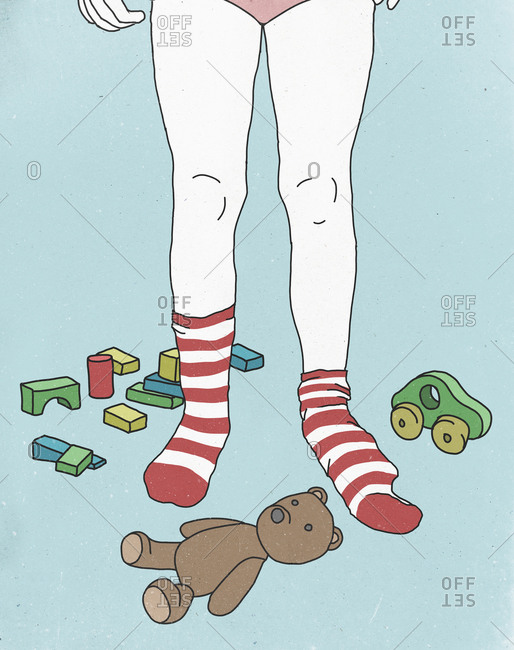 Low section of girl wearing socks while surrounded by toys against colored background
